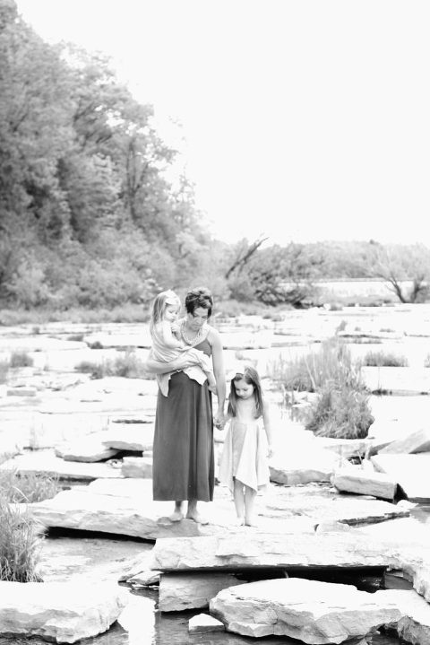 Holding hands mother and girls walking candid river outdoors